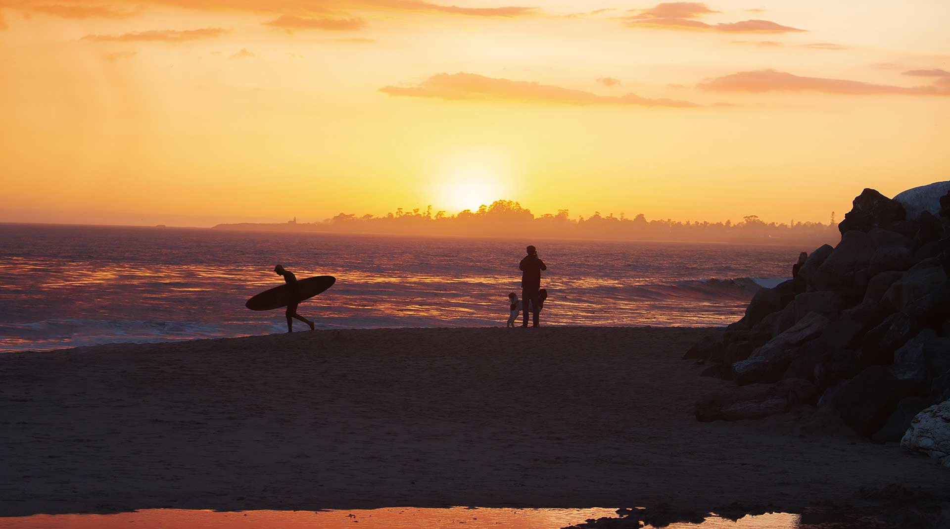 Picture of People on the Beach at Sunset in our Beach House Rentals.